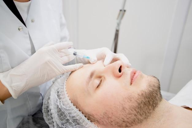 Косметологи делают уколы мужскому лицу, чтобы убрать шрамы и морщины и сделать его разглаженным.