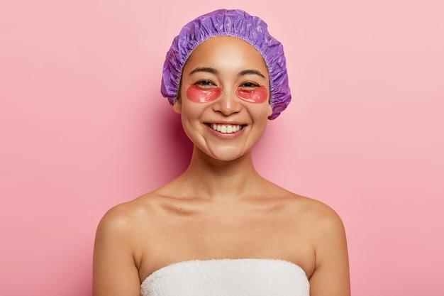 미용 및 피부 관리 개념. 쾌활한 아시아 여성이 긍정적으로 미소 짓고, 눈 아래에 하이드로 겔 패치를 적용하고, 샤워 캡을 착용하고, 셔츠가없고, 흰 수건에 싸여 있고, 분홍색 벽에 절연되어 있습니다.