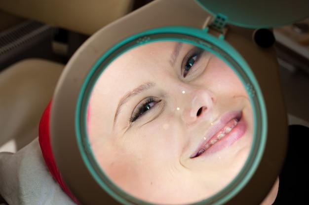 Косметология. красивая девушка в увеличительном стекле.