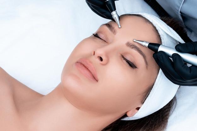 Косметология. красивая женщина в спа-клинике, получающих стимулирующее электрическое лечение лица от терапевта. крупным планом молодых женское лицо во время микротоковой терапии Premium Фотографии