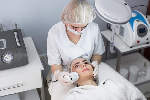 美容。顔の皮膚の超音波キャビテーションを受ける美女。超音波キャビテーションマシンを使用してアンチエイジング化粧品を受け取る女性の顔のクローズアップ。ボディケア