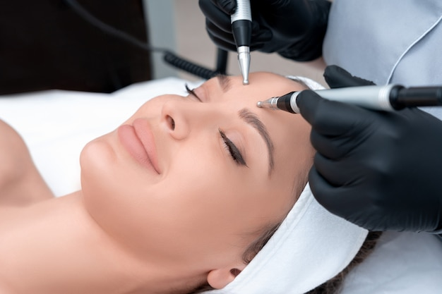 Cosmetology. beautiful woman at spa clinic receiving stimulating electric facial treatment from therapist. closeup of young female face during microcurrent therapy