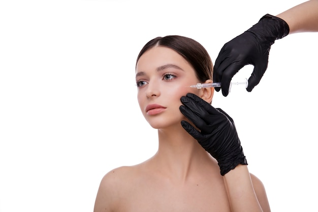 美容の美しさの概念注射器を作る注射器で美しい若い女性の顔と手
