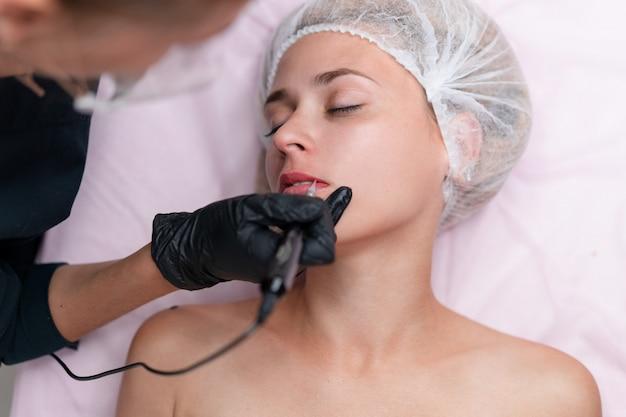 Клиент кабинета косметологии лежит на диване. косметолог наносит маркировку на губы.
