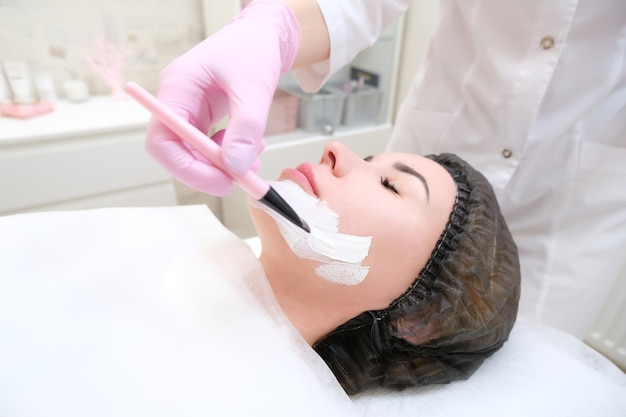 Cosmetology. close up picture of lovely young woman with closed eyes receiving facial cleansing procedure in beauty salon.