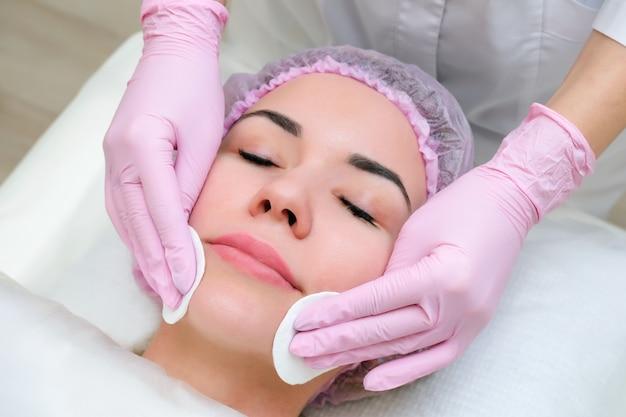 Косметология. крупным планом изображение прекрасной молодой женщины с закрытыми глазами, получающих процедуру очищения лица в салоне красоты.