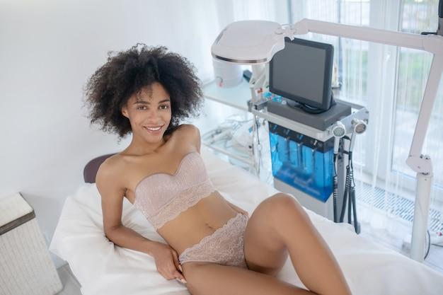 Косметология. радостная молодая женщина в нижнем белье, лежа на белом диване в массажном кабинете, ждет процедуры
