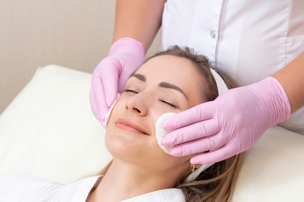 Cosmetology. lovely young woman with closed eyes receiving facial cleansing procedure in beauty salon.