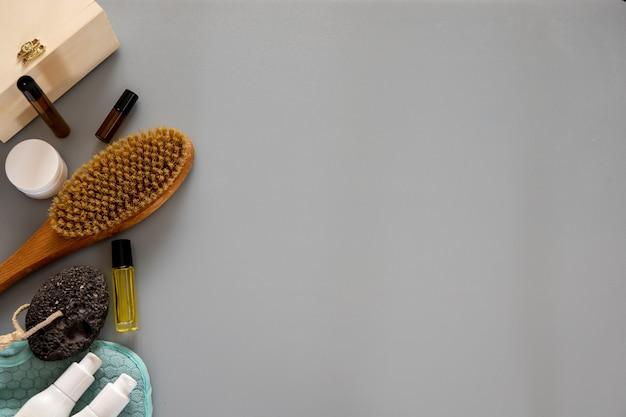 Косметология, пилинг, косметические продукты для спа, концепция красоты. натуральные ингредиенты для домашнего ухода за кожей. органическая деревянная щетка для сухого антицеллюлитного массажа, бутылка с дозатором на белом фоне.