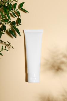 Cosmetology pink tube on minimalist beige background.