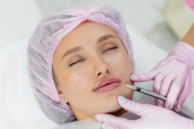 Косметологическая процедура увеличения губ и удаления морщин для молодой красивой девушки. косметология.