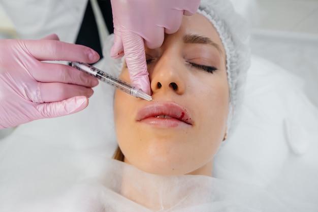 若い美しい女性のための唇の増強としわの除去のための美容手順