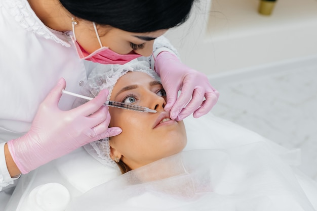 Cosmetology procedure for lip augmentation and wrinkle removal for a young beautiful girl. cosmetology.