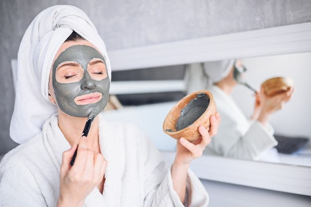 Cosmetology, skin care, face treatment, spa, natural beauty concept. beautiful smiling woman at home in bathrobe with a towel applying face clay mask against acne to rejuvenate problem skin