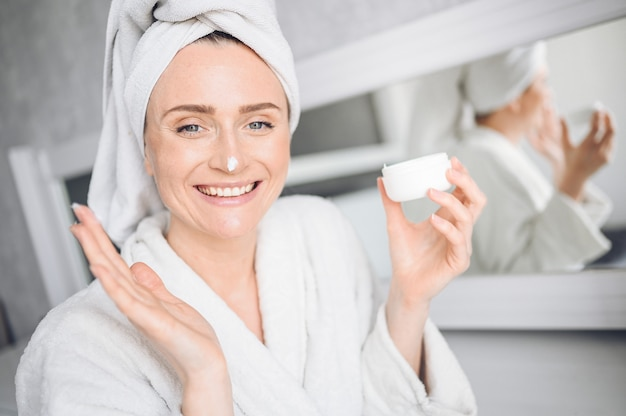 Cosmetology, skin care, face treatment, spa, natural beauty concept. beautiful smiling woman at home in bathrobe with a towel applying face moisturizing cream from white jar. beauty routine