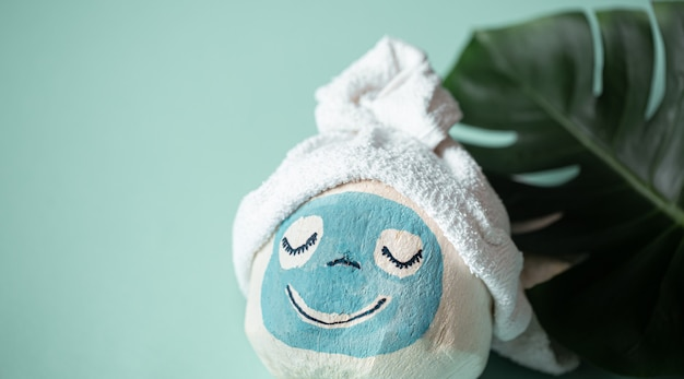 Cosmetology, skin care, face treatment, spa and natural beauty concept. coconut with creative face mask and towel on top