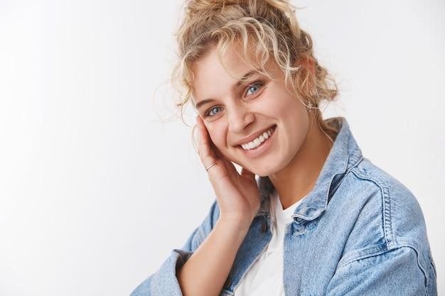 Косметология, концепция благополучия. привлекательная светловолосая европейская девушка улыбается, краснея, мило наклоняя голову, касаясь идеально чистой кожи, такой как лицо, после нанесения средства по уходу за кожей, удовлетворенная улыбка