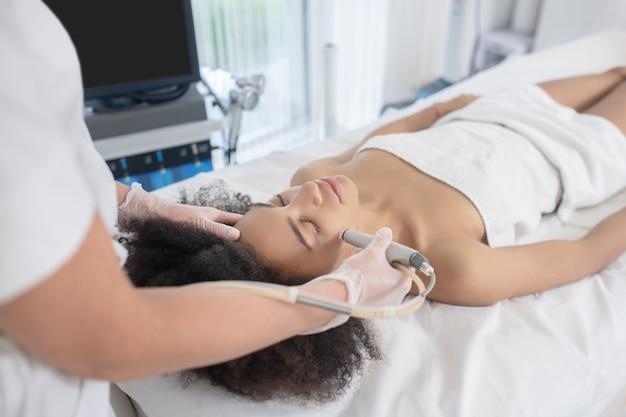 Косметология. молодая девушка с закрытыми глазами, лежащая во время косметической процедуры и косметолог, стоящий рядом с ним, держащий аппарат возле лица Premium Фотографии