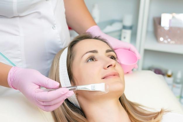 Косметология. молодая женщина, получающая процедуру очищения лица в салоне красоты. очищение лица, нанесение маски на лицо