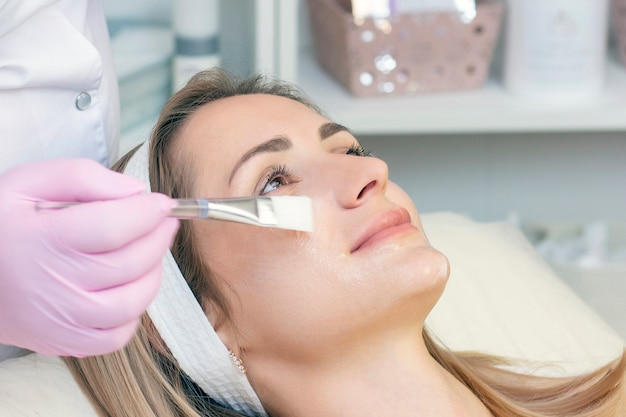 Cosmetology. young woman with receiving facial cleansing procedure in beauty salon.