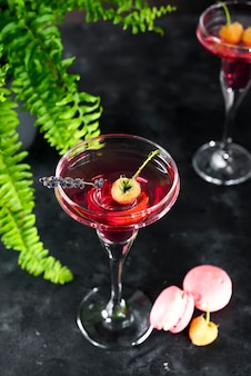 Cosmopolitan or margarita cocktail garnished with a macaroons and berries