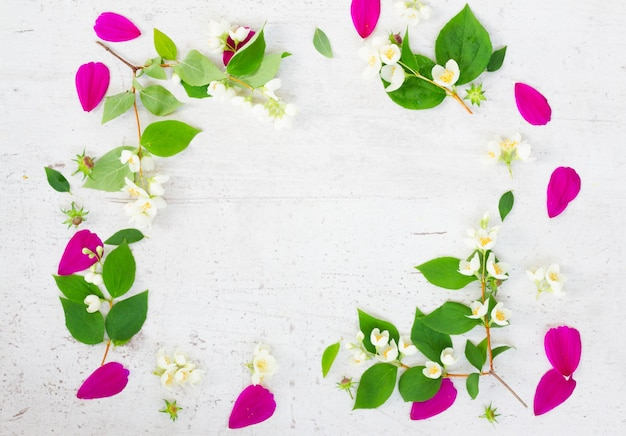 コスモスとジャスミンの生花と葉のお祝いのフラットレイフレーム構成