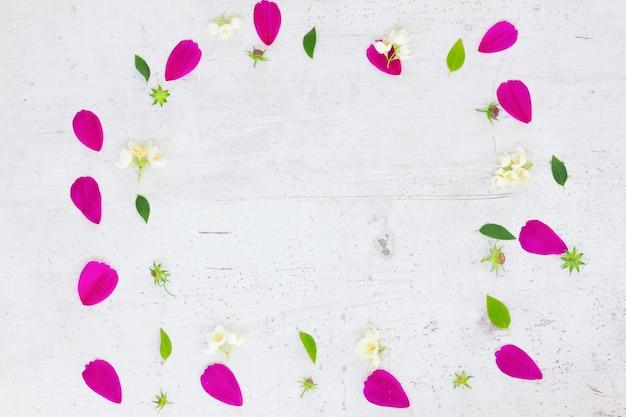 コスモスとジャスミンの新鮮な花の花びら白いテーブルの上のお祝いのフレーム構成