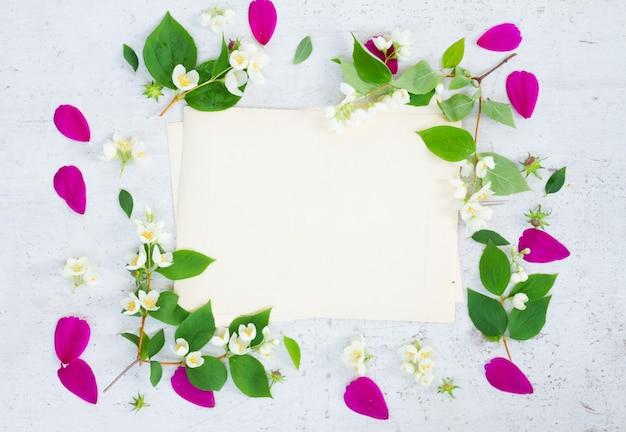 コスモスの新鮮なピンクの花と白いテーブルの上のジャスミンのお祝いフレームの構成