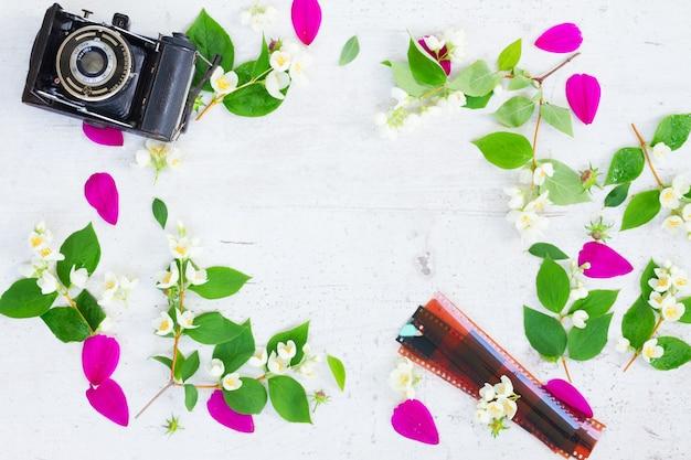 Cosmos and jasmine flowers with retro camera flat lay scene