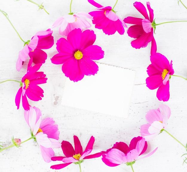Космос розовые цветы праздничная рамка композиция с бумажной запиской на белом столе
