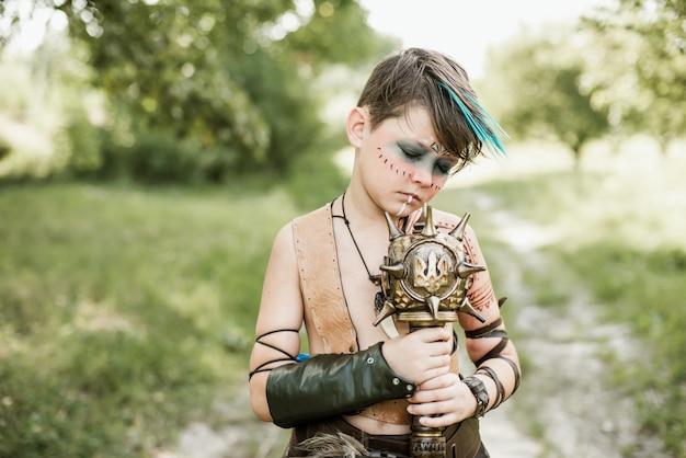 Cosplay of ukrainian kozak. cute caucasian boy holding mace with emblem of ukraine pretending to be fearless warrior.