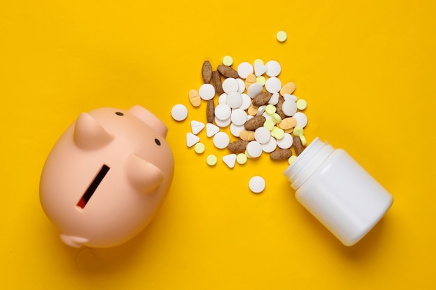 The cost of medicine. pills, piggy bank on a yellow