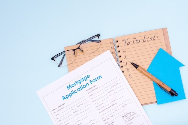 Cost planning concept. open notebook that says to-do-list pen money dollars glasses mortgage application form and small home model on pastel background, mock up, top view, flat lay, copy space