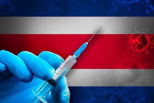코스타리카 covid19 예방 접종 캠페인 파란색 고무 장갑을 끼고 깃발 앞에 주사기를 들고 있습니다