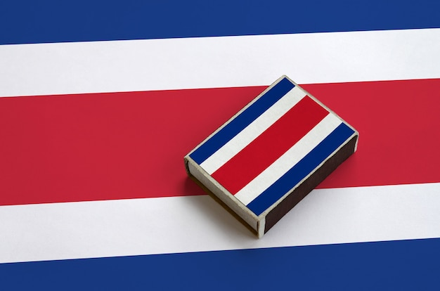 Costa rica flag  is pictured on a matchbox that lies on a large flag
