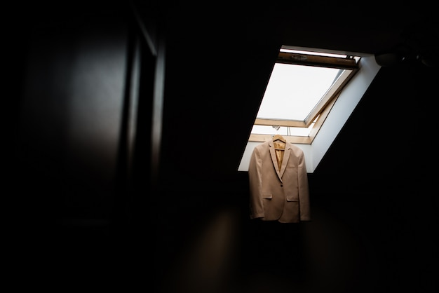 Костюмная куртка висит на окне на потолке