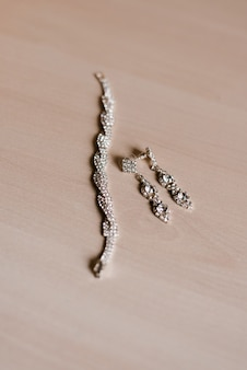 Costume jewelry: earrings and bracelet on a beige wooden table