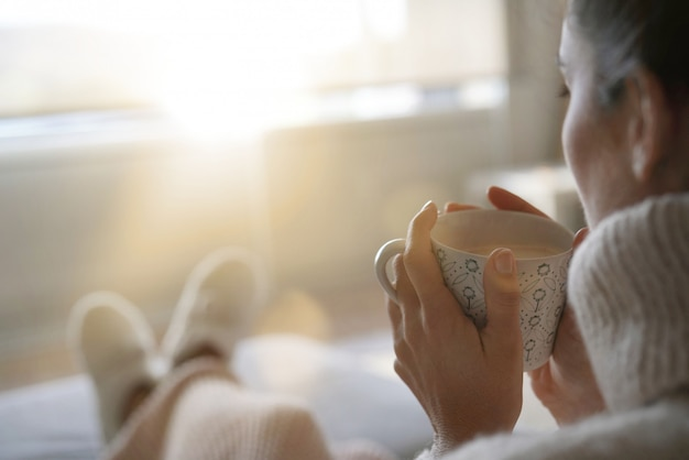 Cosy brunette at home on couch with hot drink