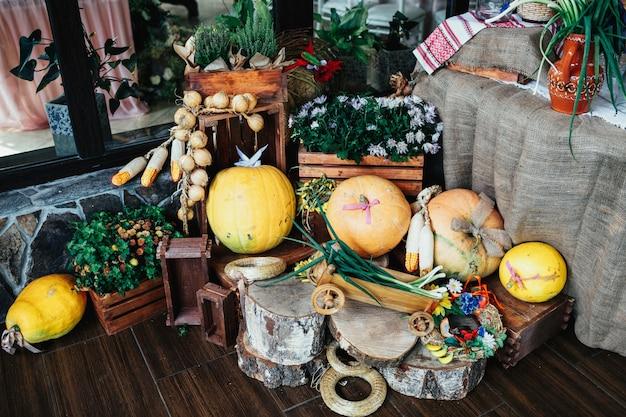 Accogliente angolo decorato con blocchi di legno, zucche e vegetazione