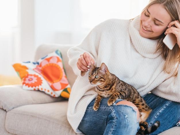 居心地の良い家庭的な雰囲気。家族のペット。電話で話している間、彼女のベンガル猫をなでる女の子。