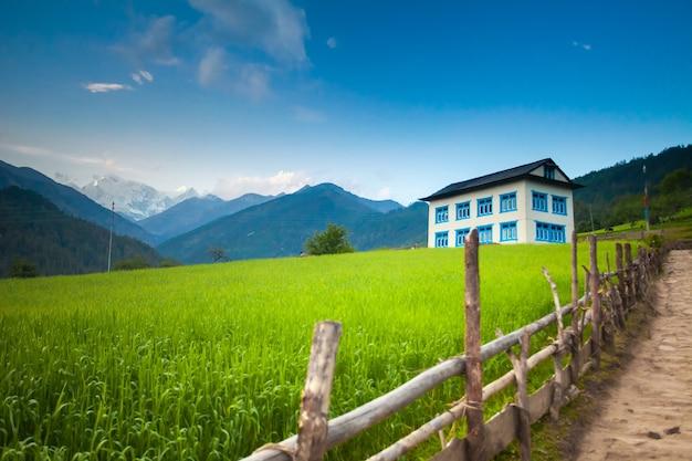 緑の草の牧草地の雪をかぶった山々の青い空に木製の柵の後ろにある居心地の良い2階建てのゲストハウス