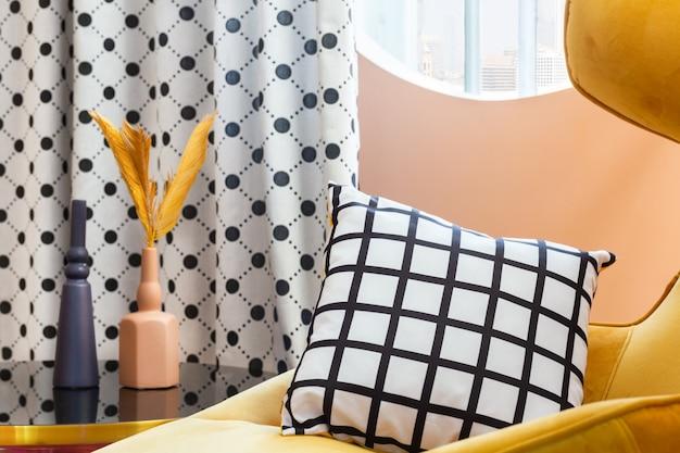 Уютное желтое кресло с полосатой черно-белой подушкой у овального окна с занавеской в горошек