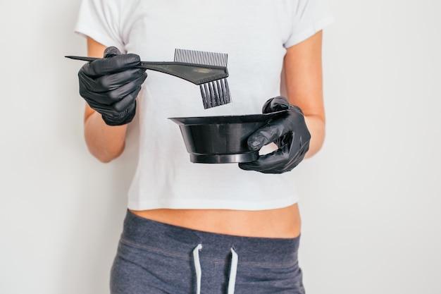 Девушка держа щетку волос и cotainer для расцветки волос в ее руке на белой предпосылке. концепция красоты.