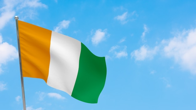 Кот-д'ивуар - флаг кот-д'ивуара на шесте. голубое небо. государственный флаг кот-д'ивуара - кот-д'ивуар