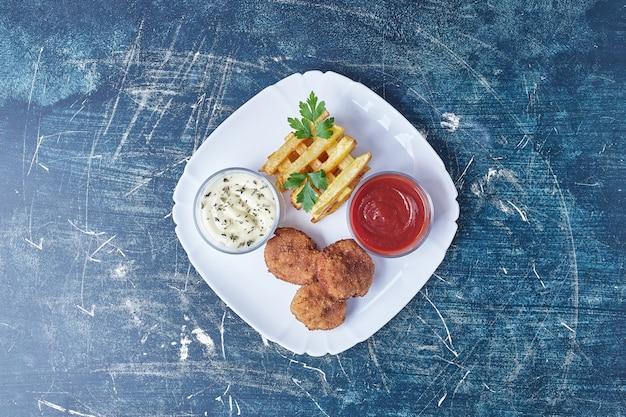Cotolette e patate fritte con erbe e salse.