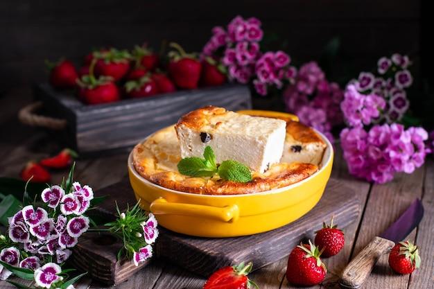 カッテージチーズは、木製の背景のベーキング皿にイチゴとケーキのキャセロールを焼きます。健康的な朝食