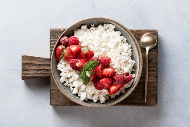 Cottage cheese bowl with berries on a light background, top view