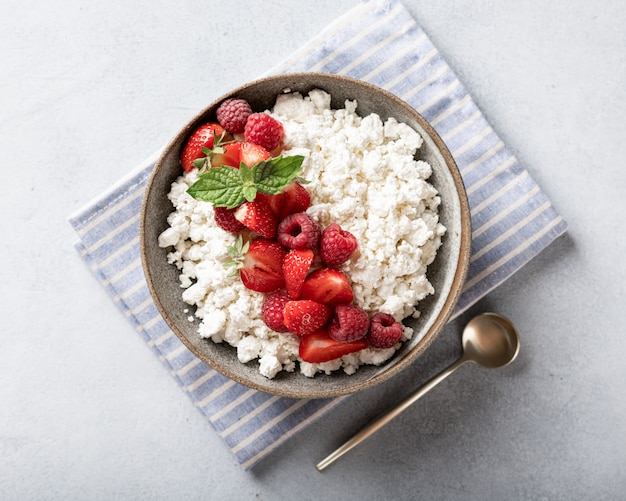 Cottage cheese bowl with berries on a light background