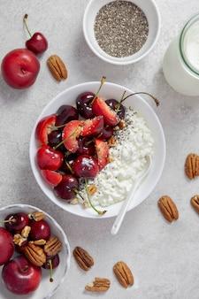 Чаша творога со свежими ягодами вишни, сливами, орехами пекан, семенами чиа и молоком на светло-серой поверхности
