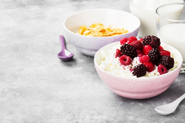 Cottage cheese in bowl with frozen raspberry and blackberry and milk in glass